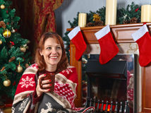 Woman with mug in the room with fireplace and Christmas decorati Royalty Free Stock Photography