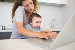 Woman multi tasking at kitchen counter Stock Images