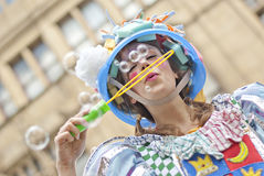 Woman in a multicolored dress blows soap bubbles on Manchester D Royalty Free Stock Photography