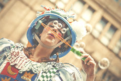 Woman in a multicolored dress blows soap bubbles on Manchester D Royalty Free Stock Images