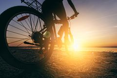 A woman in a multicolored suit sits on a bicycle in a desert area near the water. Fitness concept. Rear view and bottom view. Clos stock photos