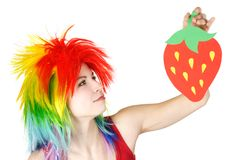 Woman in multicolored wig holding strawberry Stock Photo