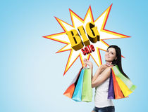 Woman with multiple shopping bags near a big sale poster on a bl Royalty Free Stock Image