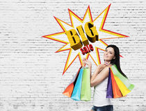 Woman with multiple shopping bags near a big sale poster on a br Stock Photography