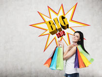 Woman with multiple shopping bags near a big sale poster Royalty Free Stock Image