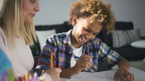 Woman mum helping to her son prepare school homework. Attentively woman mom wearing in casual clothes helping to her funky and cute son prepare school homework stock video