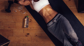 Woman with muscular abs lying on yoga mat at gym. Top view of young woman with muscular abs lying on yoga mat in gym. Cropped shot of fitness woman relaxing Stock Photos