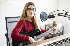 Woman music artist broadcasting a podcast episode. Attractive young woman with guitar, piano and mic making an eye contact, recording a new podcast Stock Image