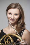 Woman musician with french horn Stock Photo