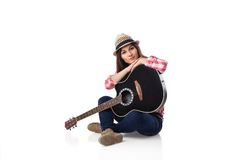 Woman musician with guitar sitting on floor. Stock Photo