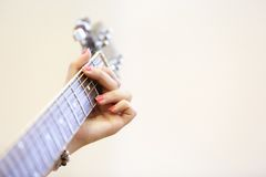 Woman musician holding a guitar, playing a G chord Stock Photos