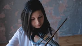 Woman musician performs with a modern electro-violin. Woman musician performs with modern electro-violin stock footage