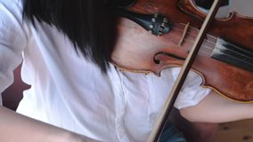 Woman musician in white shirt playing the violin. Woman musician in a white shirt playing the violin stock footage