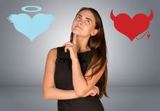 Woman musing between angel and devil hearts. On gray background royalty free stock photo
