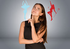 Woman musing between angelic and devilish figures. On gray background stock image