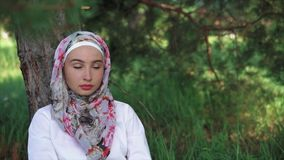 A woman in a Muslim headscarf sitting on the grass near a tree in the park stock footage