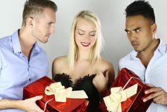 Woman must choose one of men. competition of boyfriends with gifts stock photos