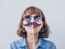 Woman with mustache. Beautiful asian woman short hair wearing blue jeans shirt and sunglasses smiling with fake mustache isolated on white background stock image