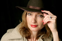 Woman of Mystery. A beautiful, sexy woman wearing a trenchcoat and fedora hat Stock Photo