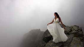 Woman on mystical mountain top. Young bride in white dress standing on rocky mountain peaks surrounded by fog Stock Photos