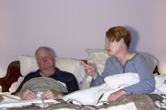 Woman Nagging Husband in Bed Royalty Free Stock Photo