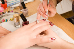 Woman with nail brush drawing on nails Stock Photography