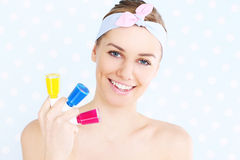 Woman with nail polish. A picture of a young woman posing with three nail polish colours Stock Photo