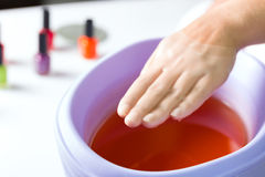 Woman in nail salon having paraffin bath stock images