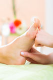Woman in nail salon receiving foot massage Royalty Free Stock Photo