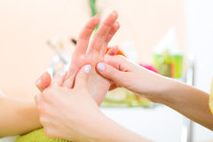 Woman in nail salon receiving hand massage Royalty Free Stock Images
