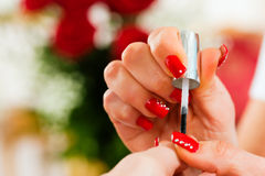 Woman in nail salon receiving manicure Stock Photo