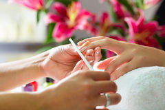Woman in nail salon receiving manicure Stock Photos
