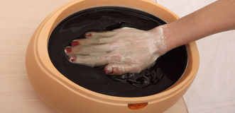 Woman in nail salon receiving manicure, she is bathing Stock Image