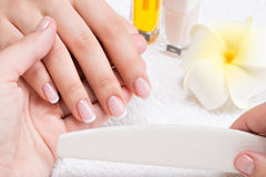 Woman in a nail salon receiving manicure royalty free stock image