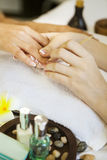 Woman in nail salon receiving manicure by beautician Royalty Free Stock Image