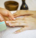 Woman in nail salon receiving manicure by beautician Stock Images