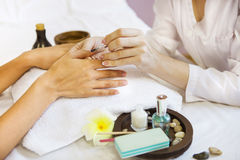 Woman in nail salon receiving manicure by beautician Royalty Free Stock Photo