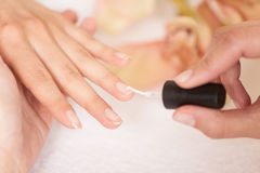 Woman in nail salon receiving manicure by beautician. Royalty Free Stock Images