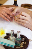 Woman in nail salon receiving manicure by beautician Stock Photo