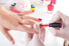 Woman in nail salon receiving manicure by beautician. closeup of female hand resting on white towel stock image