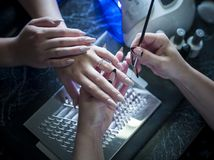 Woman in a nail salon receiving a manicure by a beautician with nail file woman Stock Photos
