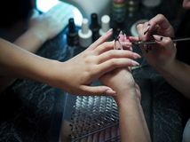 Woman in a nail salon receiving a manicure by a beautician with nail file woman Stock Images
