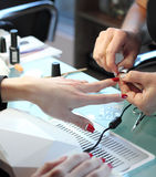 Woman in nail salon receiving manicure by beautician. Woman getting manicure at beauty salon Stock Images