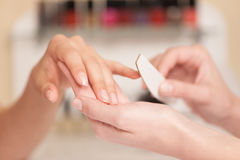 Woman in nail salon receiving manicure. Royalty Free Stock Images