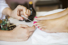 Woman in nail salon receiving pedicure by beautician Royalty Free Stock Photo