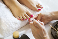 Woman in nail salon receiving pedicure by beautician Stock Photography