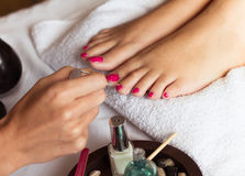 Woman in nail salon receiving pedicure by beautician Stock Image