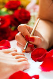 Woman in nail studio receiving pedicure Stock Images
