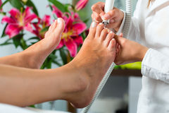 Woman in nail studio receiving pedicure Royalty Free Stock Image