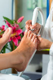 Woman in nail studio receiving pedicure Royalty Free Stock Photography